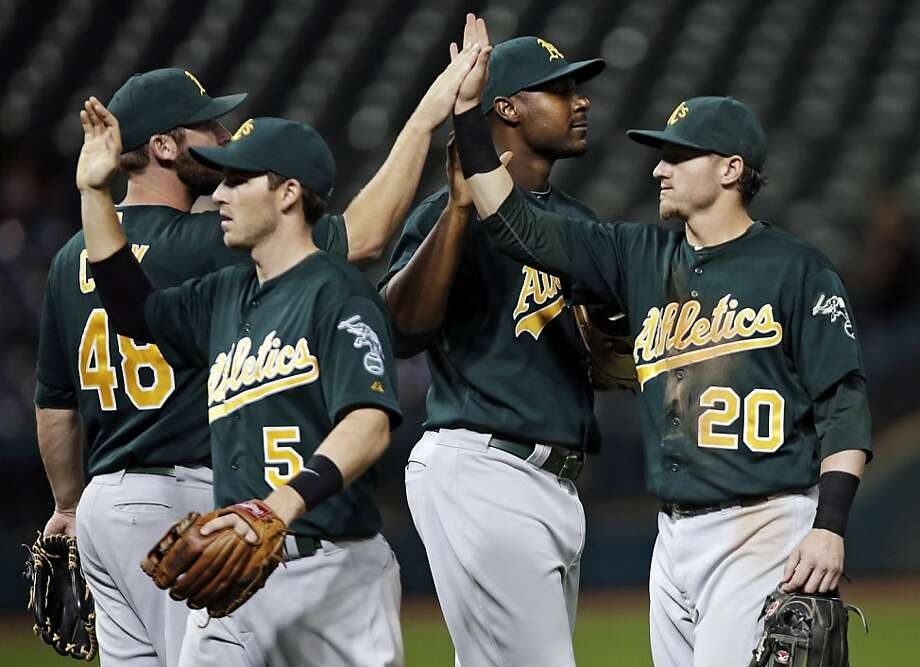 Oakland Athletics' Josh Donaldson (20) celebrates with Ryan Cook (48), Stephen Drew (5) and Chris Carter after their 8-4 win over the Cleveland Indians in a baseball game, Wednesday, Aug. 29, 2012, in Cleveland. (AP Photo/Mark Duncan) Photo: Mark Duncan, Associated Press