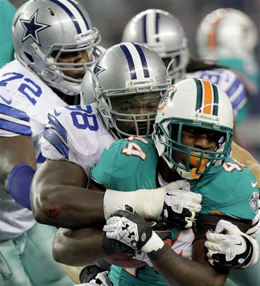 Miami Dolphins running back Lamar Miller (44) is tackled by Dallas Cowboys safety Eddie Whitley (38) and defensive tackle Rob Callaway (72) during the second half of a preseason NFL football game, Wednesday, Aug. 29, 2012, in Arlington, Texas. (AP Photo/LM Otero) Photo: LM Otero, Associated Press / AP