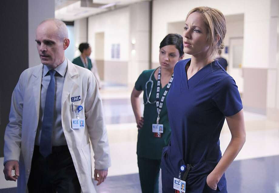 Jordana Spiro (right) plays a Chicago physician who administers to mafiosi in the drama, which co-stars {Zcaron}eljko Ivanek (left) and Floriana Lima. Photo: Nathaniel Bell, Fox