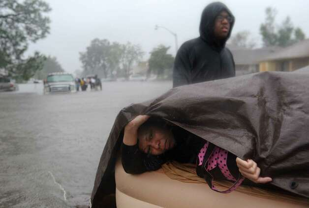 Keilani Brown who is 8 months pregnant is rescued from her home on a air bed from the Cambridge Neighborhood in LaPlace, Louisiana  with help from Walker Russell, back. The state sent scores of buses and dozens of high-water vehicles to help evacuate about 3,000 people from St. John the Baptist Parish after Tropical Storm Isaac pushed water from lakes Pontchartrain and Maurepas into parts of LaPlace. (AP Photo/Arthur D. Lauck, The Advocate) Photo: Arthur D. Lauck, Associated Press / The Advocate
