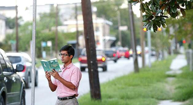 "Abhinav Kumar reads ""Moominpappa  at Sea"" as he waits for his bus at the corner of Crockett Street and Goliad in Houston on Thursday, Aug. 30, 2012. . Photo: Nick De La Torre"