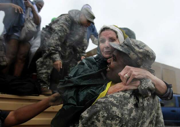 Helen Blouin holds on tight to Sgt. Julius Cage with the Louisiana National Guard as she is off loaded at a shelter in La Place, Louisiana. The state sent scores of buses and dozens of high-water vehicles to help evacuate about 3,000 people from St. John the Baptist Parish after Tropical Storm Isaac pushed water from lakes Pontchartrain and Maurepas into parts of LaPlace. (AP Photo/Arthur D. Lauck, The Advocate) Photo: Arthur D. Lauck, Associated Press / The Advocate