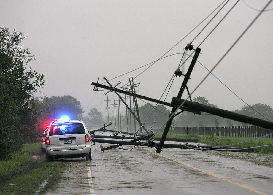 Lafourche Parish Sheriffís Office vehicles drive pass downed power lines Wednesday near the Valentine Bridge Wednesday, Aug. 29, 2012, in Houma, La. (AP Photo/The Houma Daily Courier, Abby Tabor) Photo: Abby Tabor, Associated Press / The Houma Daily Courier