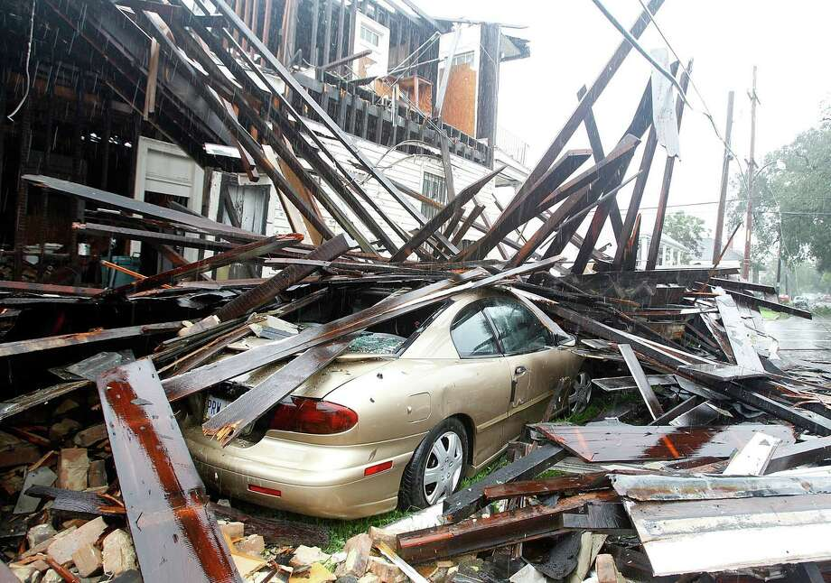 A house at the corner of N. Miro and Columbus Streets in New Orleans collapsed during the height of the Hurricane Isaac destroying three vehicles that where parked alongside it, Wednesday, Aug. 29, 2012. (AP Photo/The Times-Picayune, David Grunfeld) Photo: David Grunfeld, Associated Press / The Times-Picayune