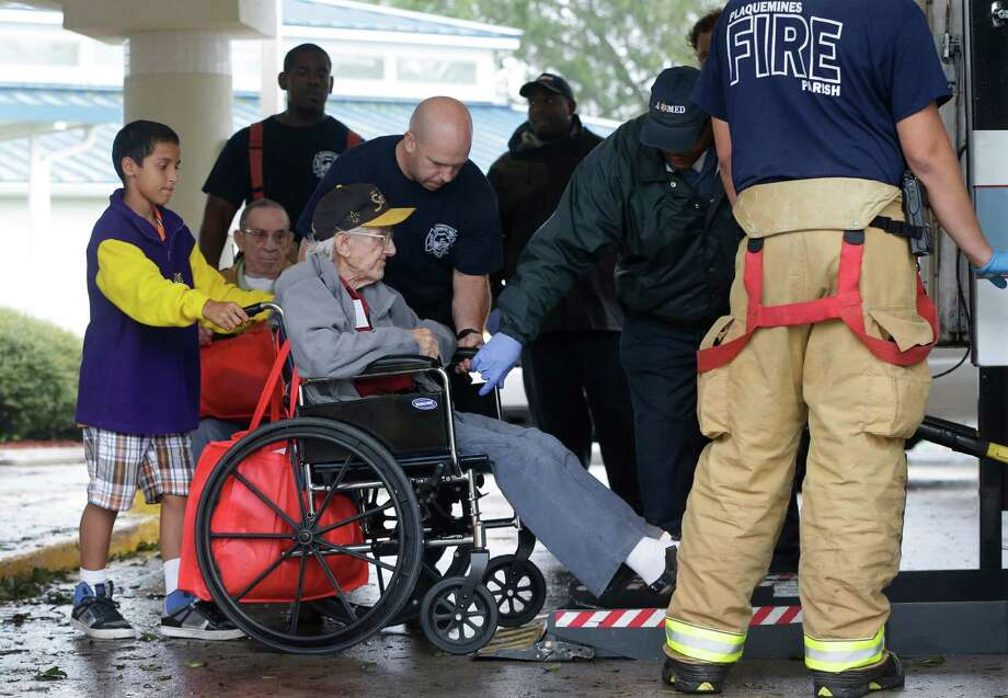 Trevelle Bivalacqua, 12, left, helps fire fighters and other volunteers evacuate residents from the Riverbend Nursing Center as Hurricane Isaac makes landfall, Wednesday, Aug. 29, 2012, in Jesuit Bend, La. Plaquemines Parish ordered a mandatory evacuation for the west bank of the Mississippi below Belle Chasse because of worries about a storm surge. The order affected about 3,000 people. (AP Photo/Eric Gay) Photo: Eric Gay, Associated Press / AP