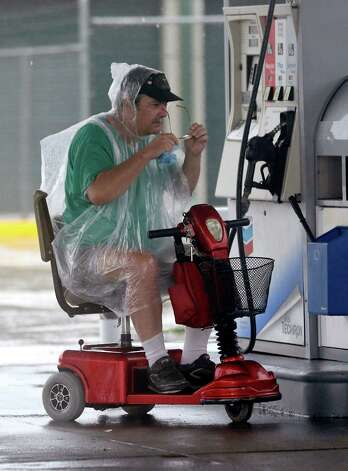 Michael Ferbosses stops at a gas station to get a towel to wipe off his glasses as he makes his way home in the wind and rain from Isaac in Chalmette, La.,Thursday, Aug. 30, 2012. Isaac's maximum sustained winds had decreased to 45 mph and the National Hurricane Center said it was expected to become a tropical depression by Thursday night. The storm's center was on track to cross Arkansas on Friday and southern Missouri on Friday night, spreading rain as it goes.  (AP Photo/David J. Phillip) Photo: David J. Phillip, Associated Press / AP