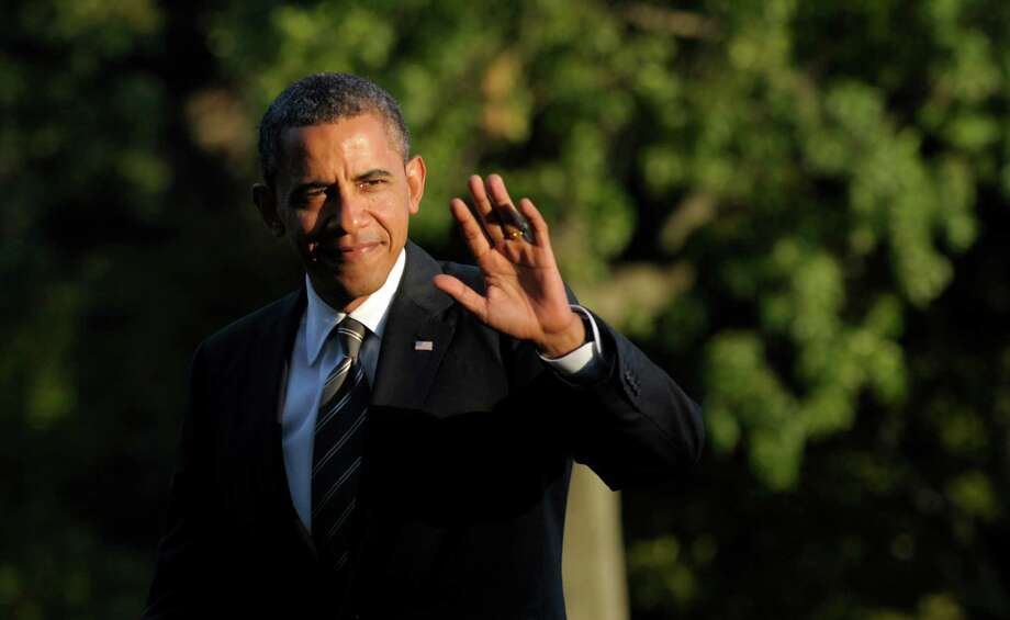 President Barack Obama waves as he walks from Marine One on the South Lawn of the White House in Washington, Wednesday, Aug. 29, 2012, after returning from campaigning. (AP Photo/Susan Walsh) Photo: Susan Walsh, STF / AP