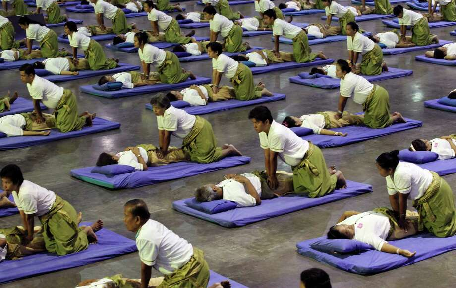 Thai masseuses perform mass massaging at a sport arena on the outskirts of Bangkok, Thailand Thursday, Aug. 30, 2012. Thailand has long been known as the massage capital of the world. Now, it has a Guinness World Record to prove it when some 641 massage therapists mass-massaged 641 people simultaneously for 12 minutes to win the honor Thursday at an indoor arena in Bangkok. The event was organized by the Health Ministry to promote the Southeast Asian nation's massage and spa industry. Photo: Apichart Weerawong, AP / AP