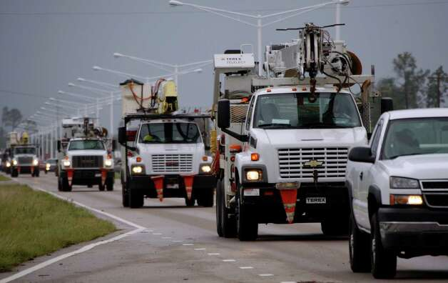 A steady armada of utility service trucks drive through Waveland, Miss., to assist  residents left without power from Hurricane Isaac, Thursday, Aug. 30, 2012. Signs of life returned to the Mississippi Gulf Coast on Thursday as curfews were lifted and some businesses and roads reopened, but many residents still couldn't make it home because of flooding in low lying areas and along rivers. (AP Photo/Rogelio V. Solis) Photo: Rogelio V. Solis, Associated Press / AP