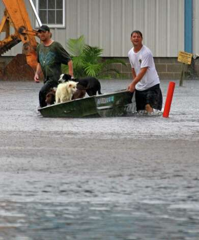 Waveland, Miss., residents wade through storm waters left from Isaac's unceasing rainstorms to seek shelter, Thursday, Aug. 30, 2012. Signs of life returned to the Mississippi Gulf Coast on Thursday as curfews were lifted and some businesses and roads reopened, but many residents still couldn't make it home because of flooding in low lying areas and along rivers.  (AP Photo/Rogelio V. Solis) Photo: Rogelio V. Solis, Associated Press / AP