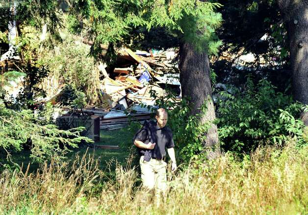 An investigator walks behind the Sunny Valley Road house that exploded in New Milford as seen from the neighbor's yard. Photographed Thursday, Aug. 30, 2012. Photo: Michael Duffy