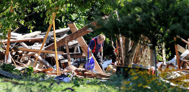 Investigators sift through the rubble Thursday morning, Aug. 30, 2012, after a propane explosion leveled a house on Sunny Valley Road in New Milford Wednesday night. Photo: Carol Kaliff
