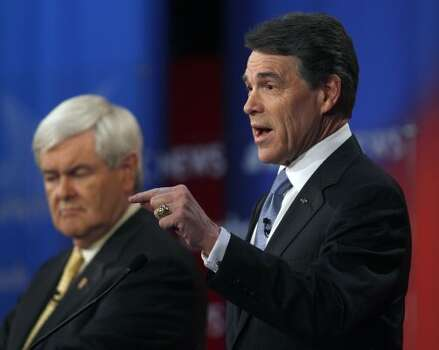 Rick Perry answers a question as Newt Gingrich listens in the background during a Republican presidential candidate debate at the Capitol Center for the Arts in Concord, N.H., Sunday, Jan. 8, 2012. (Charles Krupa / Associated Press)
