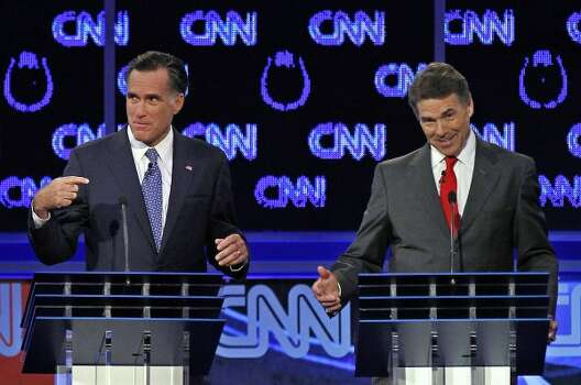 Mitt Romney and Rick Perry spar during a Republican presidential debate in Las Vegas. (Chris Carlson / Associated Press)