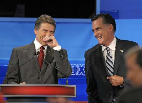 Rick Perry and Mitt Romney share a laugh during a Fox News/Google debate Thursday, Sept. 22, 2011, in Orlando, Fla. (Phelan M. Ebenhack / Associated Press)