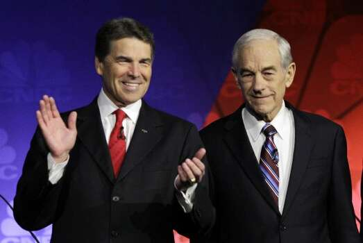 Rick Perry and Ron Paul, R-Texas are seen before a Republican presidential debate at Oakland University in Auburn Hills, Mich., Wednesday, Nov. 9, 2011. (Paul Sancya / Associated Press)