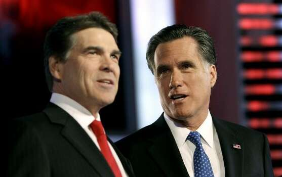 Rick Perry and Mitt Romney talk prior to the Republican debate, Saturday, Dec. 10, 2011, in Des Moines, Iowa. (Charlie Neibergall / Associated Press)