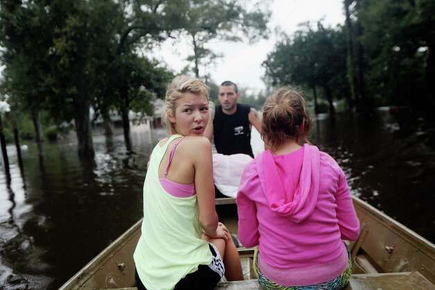 SLIDELL, LA - AUGUST 30:  Kylie Trumbaturi (L) and her sister Brittany depart their flooded home with family member Joshua Barbot (C) who came to rescue family members in a boat on August 30, 2012 in Slidell, Louisiana. The large Category 1 hurricane had slowly moved across southeast Louisiana, dumping huge amounts of rain and knocking out power to Louisianans in scattered parts of the state. The weather system has now been downgraded to a tropical storm but is still producing heavy rains and flooding as it moves north. Photo: Mario Tama, Getty Images / 2012 Getty Images