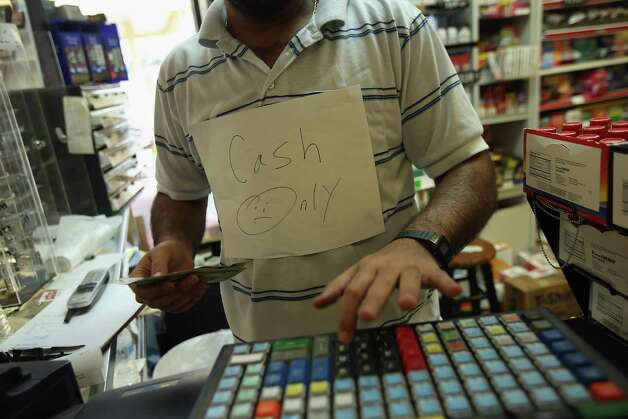 "SLIDELL, LA - AUGUST 30:  Fanous Kamel rings up a ""cash only"" order for groceries at Redfish Traders, one of the few stores open following the passing of Hurricane Isaac on August 30, 2012 in Slidell, Louisiana in St. Tammany Parish. Although the weather system, now downgraded to a tropical storm, had moved north, heavy rains flooded Bayou Pattasat, which backed up into Slidell, northeast of New Orleans. Photo: John Moore, Getty Images / 2012 Getty Images"