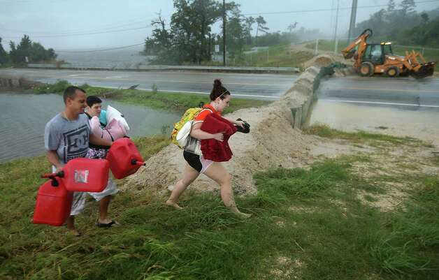 SLIDELL, LA - AUGUST 30:  Residents carry pillows, blankets and fuel containers past a flood berm while evacuating an area of rising waters from Hurricane Isaac on August 30, 2012 in Slidell, Louisiana in St. Tammany Parish. Although the weather system, now downgraded to a tropical storm, had moved north, heavy rains flooded Bayou Pattasat, which backed up into the town north of New Orleans. Photo: John Moore, Getty Images / 2012 Getty Images