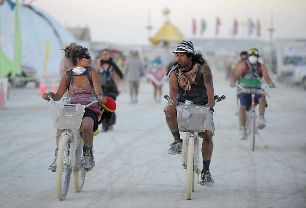 Burners ride their bicycle through the streets of Burning Man near Gerlach, Nev. on Aug. 28, 2012. Photo: Andy Barron, Associated Press