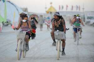 Burners ride their bicycle through the streets of Burning Man near Gerlach, Nev. on Aug. 28, 2012.