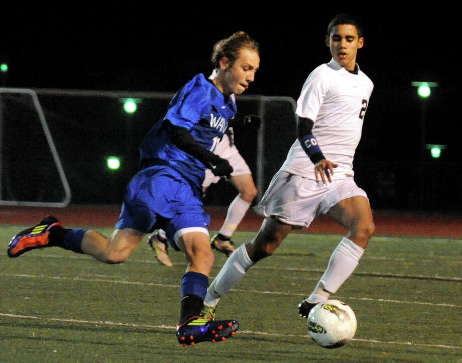Darien's #11 Spencer McMullin rushes to control the ball, during FCIAC boys' soccer semi-finals action in Fairfield, Conn. on Wednesday November 2, 2011. At right is Trumbull's #2 Jonathan DeJesus. Photo: Christian Abraham / Connecticut Post