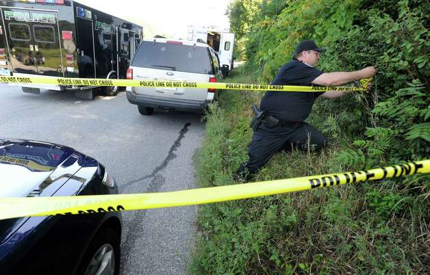 New Milford Police Officer Rob Tozzi blocks off the area on Sunny Valley Road in New Milford where an explosion leveled a house Wednesday evening. Photo: Carol Kaliff