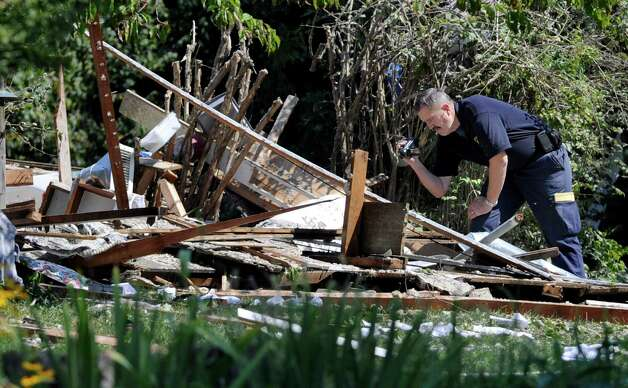 Investigators sift through the rubble of a home on Sunny Valley Road in New Milford Thursday, Aug. 30, 2012, that was leveled by the explosion of a propane explosion Wednesday evening. Photo: Carol Kaliff