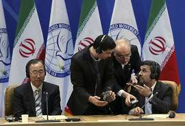 In this picture taken by semi-official Mehr News Agency, U.N. Secretary-General Ban Ki-Moon, left, looks on as Iranian President Mahmoud Ahmadinejad, right, confers with Foreign Minister Ali Akbar Salehi, center, and an unidentified man at summit of the Nonaligned Movement as  in Tehran, Iran, Thursday, Aug. 30, 2012. (AP Photo/Raouf Mohseni, Mehr News Agency)