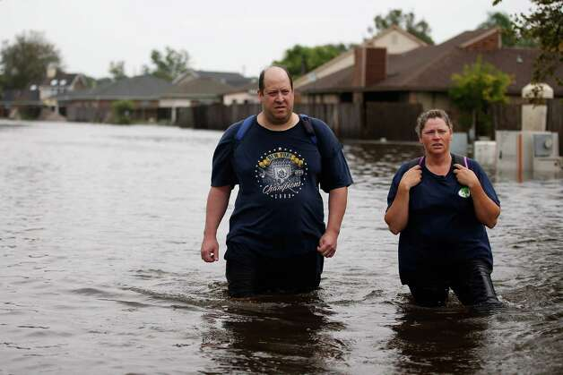 LAPLACE, LA - AUGUST 30:  Keith and Leslie Robertson walk through flood water after checking on their house the Indigo Lakes subdivion on August 30, 2012 in LaPlace, Louisiana  . The large Category 1 hurricane had slowly moved across southeast Louisiana, dumping huge amounts of rain and knocking out power to Louisianans in scattered parts of the state. The weather system has now been downgraded to a tropical storm but is still producing heavy rains and flooding as it moves north. Photo: Chris Graythen, Getty Images / 2012 Getty Images