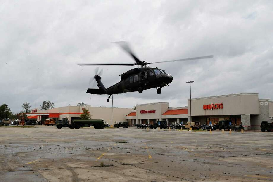 LAPLACE, LA - AUGUST 30:  A military helicopter lands in a shopping center parking lot following Hurricane Isaac on August 30, 2012 in LaPlace, Louisiana.  The large Category 1 hurricane had slowly moved across southeast Louisiana, dumping huge amounts of rain and knocking out power to Louisianans in scattered parts of the state. The weather system has now been downgraded to a tropical storm but is still producing heavy rains and flooding as it moves north. Photo: Chris Graythen, Getty Images / 2012 Getty Images