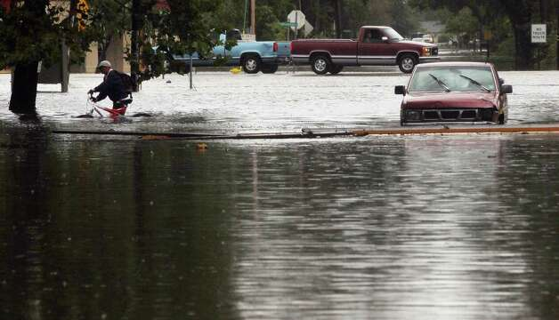 SLIDELL, LA - AUGUST 30:   A resident evacuates from flooding from Hurricane Isaac's storm surge on the north shore of Lake Ponchartrain on August 30, 2012 in Slidell, Louisiana. The large Category 1 hurricane had slowly moved across southeast Louisiana, dumping huge amounts of rain and knocking out power to Louisianans in scattered parts of the state. The weather system has now been downgraded to a tropical storm but is still producing heavy rains and flooding as it moves north. Photo: Mario Tama, Getty Images / 2012 Getty Images