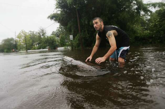 SLIDELL, LA - AUGUST 30:  Joshua Barbot moves a log while preparing to rescue family members in his boat on August 30, 2012 in Slidell, Louisiana.  Hurricane Isaac storm surge caused flooding in Slidell this morning on the north shore of Lake Ponchartrain. The large Level 1 hurricane slowly moved across southeast Louisiana, dumping huge amounts of rain and knocking out power to Louisianans in scattered parts of the state. The weather system has now been downgraded to a tropical storm but is still producing heavy rains and flooding as it moves north. Photo: Mario Tama, Getty Images / 2012 Getty Images