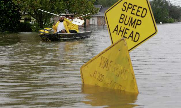 Isaac Fields, left, and Victor Jones use street signs to paddle a boat out of their flooded neighbor, Thursday, Aug. 30, 2012, in LaPlace, La. Isaac has caused major flooding in the region. (AP Photo/Eric Gay) Photo: Eric Gay, Associated Press / AP