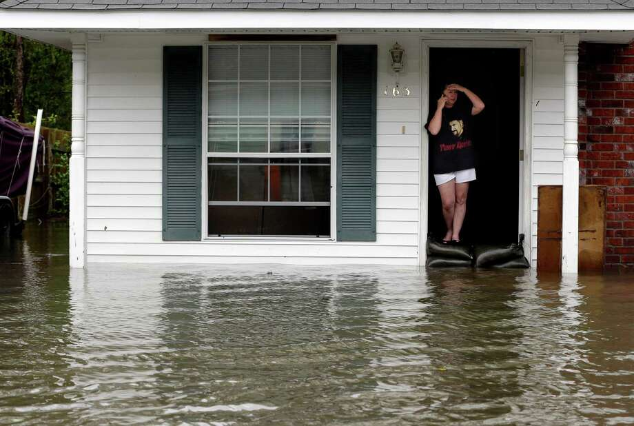 A resident whose home is surrounded by flood waters talks on the phone, Thursday, Aug. 30, 2012, in LaPlace, La. Isaac has caused major flooding in the region. (AP Photo/Eric Gay) Photo: Eric Gay, Associated Press / AP