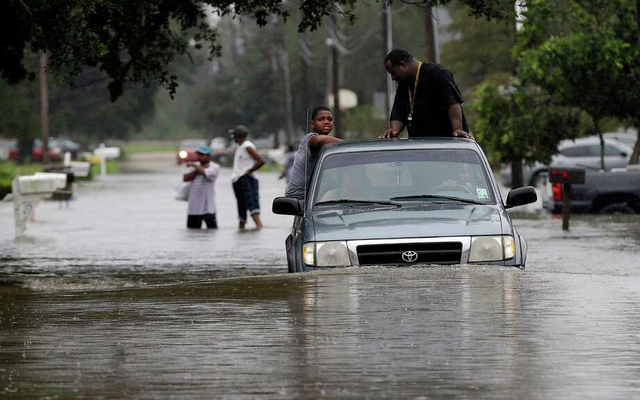 Residents evacuate their flooded neighborhood, Thursday, Aug. 30, 2012, in LaPlace, La. Isaac has caused major flooding in the region.  (AP Photo/Eric Gay) Photo: Eric Gay, Associated Press / AP
