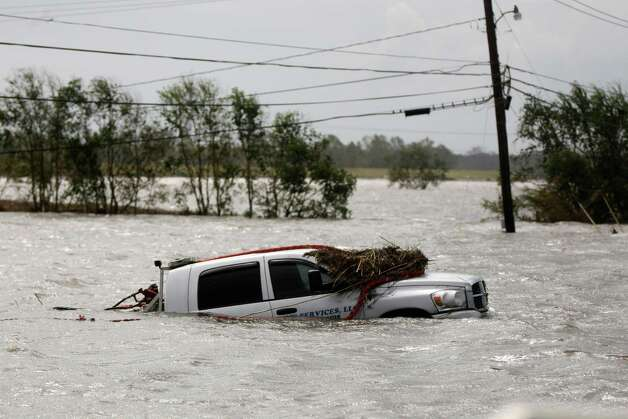 A  car sits submerged after Isaac passed through the region, in Plaquemines Parish, La., Thursday, Aug. 30, 2012.   Isaac staggered toward central Louisiana early Thursday, its weakening winds still potent enough to drive storm surge into portions of the coast and the River Parishes between New Orleans and Baton Rouge. (AP Photo/Gerald Herbert) Photo: Gerald Herbert, Associated Press / AP