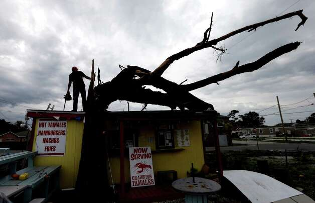 Lonney Sciortino prepares to cut down a tree which fell on top of his tamale stand during Isaac in Arabi, La.,Thursday, Aug. 30, 2012. Isaac's maximum sustained winds had decreased to 45 mph and the National Hurricane Center said it was expected to become a tropical depression by Thursday night. The storm's center was on track to cross Arkansas on Friday and southern Missouri on Friday night, spreading rain as it goes. (AP Photo/David J. Phillip) Photo: David J. Phillip, Associated Press / AP