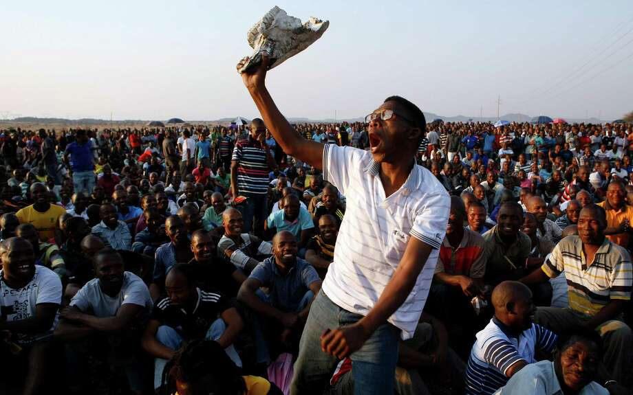 A striking miner sings and dances at a gathering Wednesday at the Lonmin Platinum Mine, which was the scene two weeks ago of a violent confrontation in which police shot and killed 34 mine workers. Photo: Themba Hadebe / AP