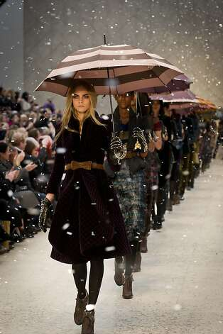 "Burberry's presentation of its 2012 autumn-winter fashions showcased models awash in gusts of fall leaves and then rain as part of a ""digital weather experience."" Photo: Burberry"