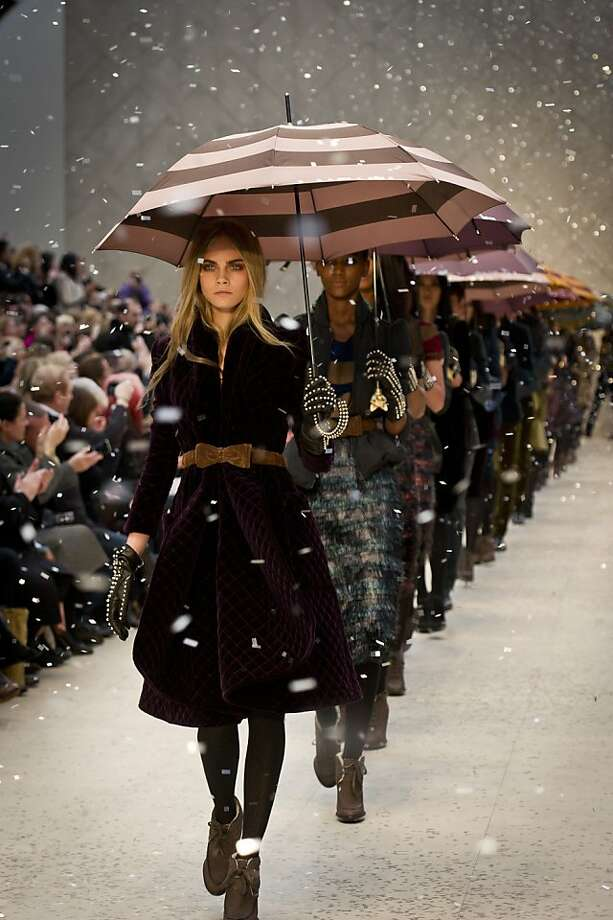 """Burberry's presentation of its 2012 autumn-winter fashions showcased models awash in gusts of fall leaves and then rain as part of a """"digital weather experience."""" Photo: Burberry"""
