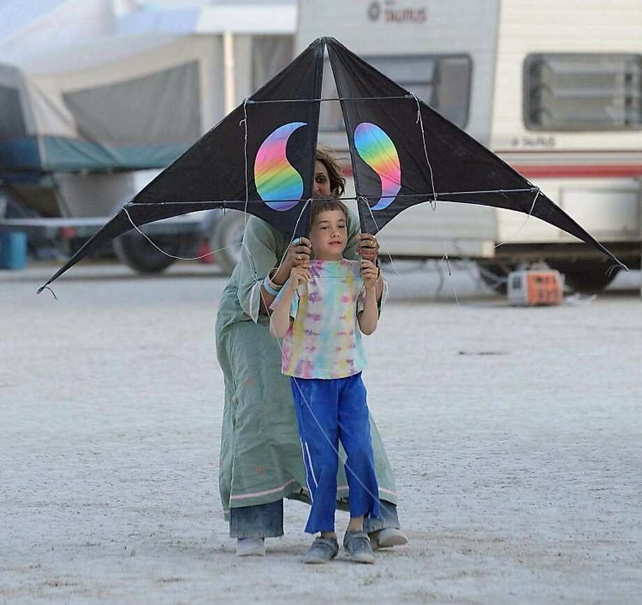 Milo Miller, 7, gets help from Niz Arif in getting a kite in the air on the Black Rock Desert, Nev. during Burning Man on Thursday, Aug. 30, 2012. Photo:  Andy Barron, Associated Press