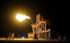 People gather around an art intallation at Burning Man in the Black Rock Desert near Gerlach, Nev. on Wednesday, Aug. 29, 2012. (AP Photo/Reno Gazette-Journal, Andy Barron)
