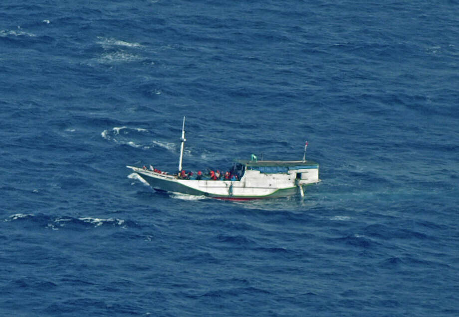 """FILE - In this July 4, 2012 file photo released by the Indonesian National Search And Rescue Agency, a wooden boat which is believed to have up to 180 asylum seekers on board floats on the waters off Christmas Island, Australia.  Australia calls it a """"closing-down sale"""" for people smugglers: Asylum-seekers in rickety boats have been reaching its shores in record numbers to avoid a tougher new deportation policy the country is preparing to implement. For many migrants, the price of haste may be death. (AP Photo/Indonesian National Search and Rescue Agency, File) Photo: Uncredited / Indonesian National Search and R"""