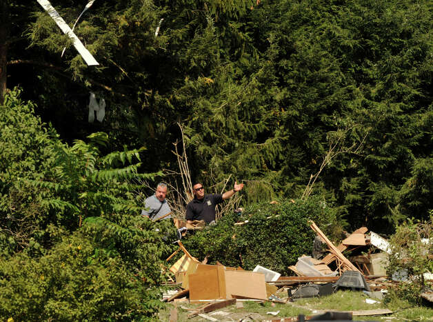 Officials survey the damage on Thursday, Aug. 30, 2012, on Sunny Valley Road in New Milford, where investigators suspect a propane explosion destroyed a home on Wednesday evening. Photo: Jason Rearick / The News-Times