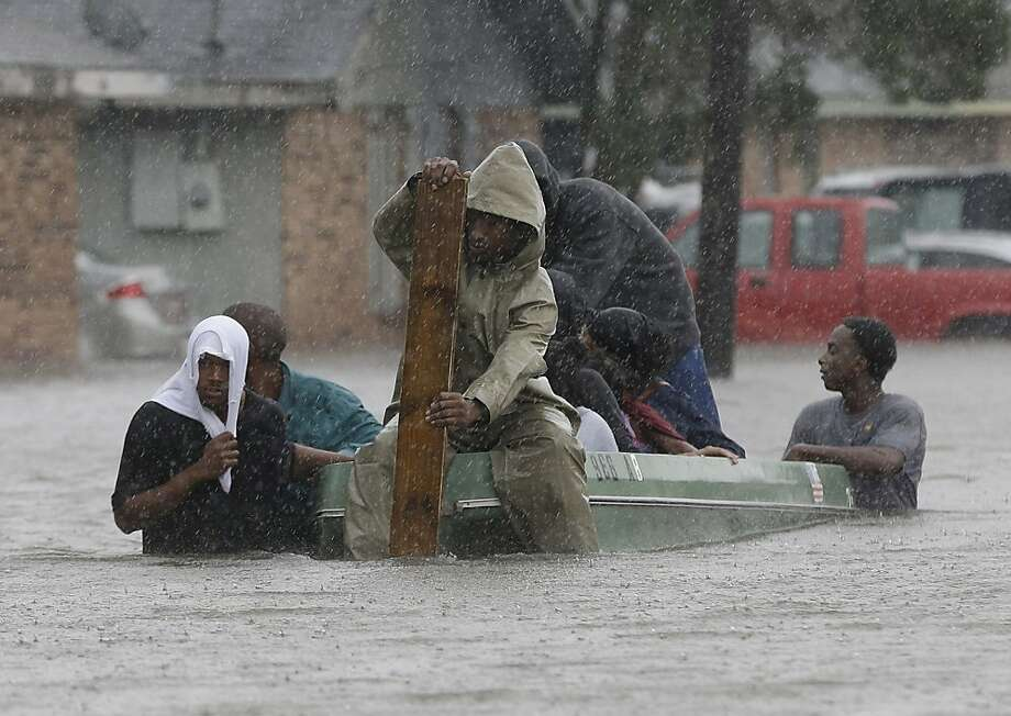 Residents evacuate their flooded neighborhood in LaPlace, La. Isaac staggered toward central Louisiana early Thursday. Photo: Eric Gay, Associated Press