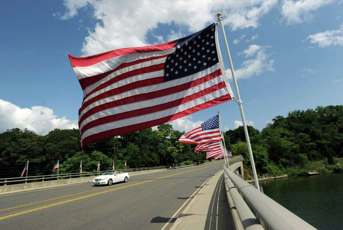 A convertible car drives past a group of American flags attached to the Post Road bridge over the Mianus River in Greenwich, Saturday afternoon, Aug. 18, 2012.