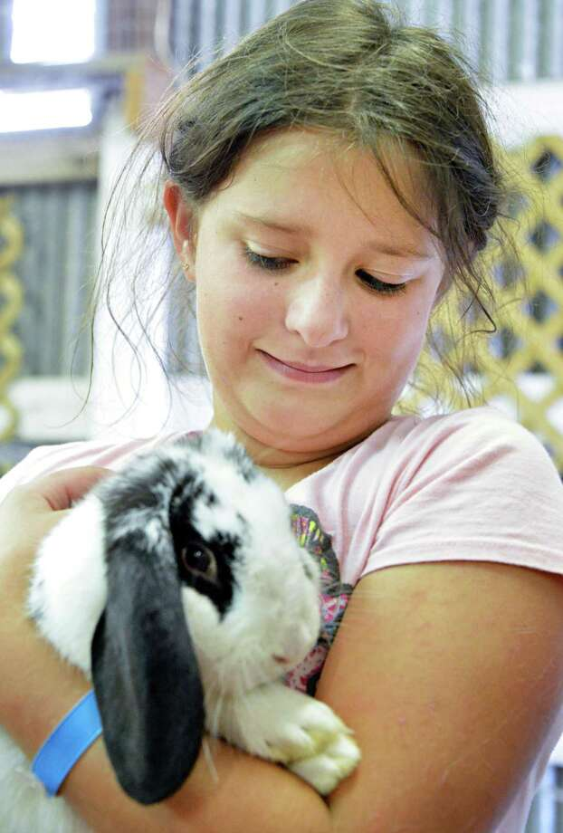 "Amanda Clifford of Esperance hugs her blue ribbon winning rabbit ""Oreo"" at the Fonda Fair at the Montgomery County Fairgrounds in Fonda Thursday Aug. 30, 2012.  (John Carl D'Annibale / Times Union) Photo: John Carl D'Annibale / 00019043A"