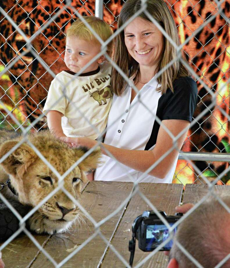 Emily Panton of Hagaman and her 14-mos.-old son Gabriel Panton have their photograph taken with an African lion cub by Patrick Clancy, at bottom, of Jungle Habitat of Maryville, Tenn, at the Fonda Fair at the Montgomery County Fairgrounds in Fonda Thursday Aug. 30, 2012.  (John Carl D'Annibale / Times Union) Photo: John Carl D'Annibale / 00019043A